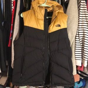 Women's black and gold North Face hooded vest